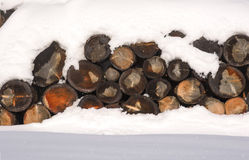 The logs woodpile in the snow in winter. Rural winter scene. HDR Stock Photos