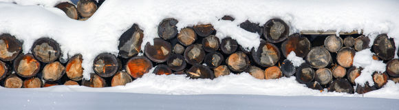 The logs woodpile in the snow in winter. Rural winter scene. HDR Royalty Free Stock Photography