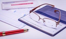 Lohn mit Kontrolle sofort, rechtzeitig Gläser auf einem Scheckheft, roter Stift, Finanzdokumente auf dem Hintergrund Nahaufnahme, lizenzfreie stockfotos
