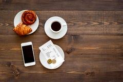 Lohnliste am Café durch Karte Bill und Bankkarte nahe Kaffee und Hörnchen auf dunklem copyspace Draufsicht des Holztischs Stockbild