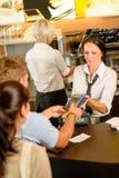 Lohnliste des Mannes am Kaffee unter Verwendung der Karte Stockfoto