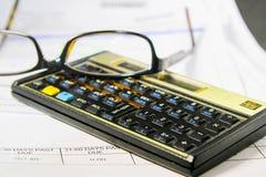 Lohnlisten mit einem Taschenrechner und Lesebrille stockfoto