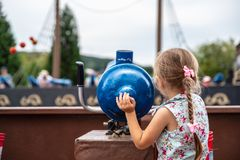Loifling, Germany - 26 July, 2018: Little girl plays near toy cannon on Pirates of Caribbean attraction in Churpfalzpark royalty free stock photos