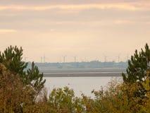 Loin outre de l'horizon au-dessus de la mer de l'eau de côte avec le silhouett de turbine de vent photographie stock libre de droits