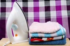 LoinclothPile av färgrik kläder och elektriskt järn på höftskynske Fotografering för Bildbyråer
