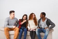 Loisirs et temps de partie, amis s'asseyant sur le divan Photos libres de droits