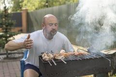 Loisirs, nourriture, les gens et concept de vacances - jeune homme heureux faisant cuire la viande sur le gril de barbecue à la p Images libres de droits