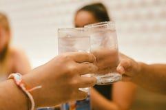 Loisirs, vacances, mangeant, concept de personnes et de nourriture - amis dînant au restaurant et faisant tinter des boissons image stock