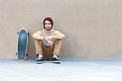 Loitering Skateboarder. Handsome skateboarder haning around, sitting against a granite wall, with his skateboard next to him Stock Images