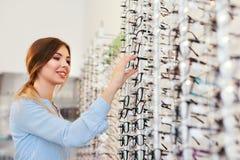 Loja ótica Mostra próxima da mulher que procura monóculos fotografia de stock