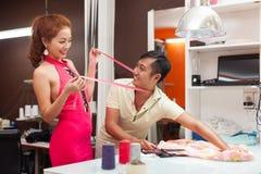 Loja asiática do alfaiate do homem do desenhista que trabalha na tabela foto de stock