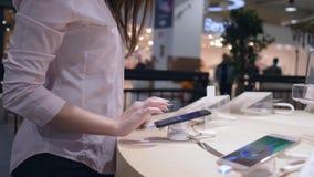 A loja da eletrônica, cliente fêmea smartphone moderno seleciona e da teste perto da mostra video estoque