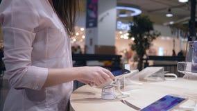 A loja da eletrônica, comprador atrativo da menina telefone celular moderno seleciona e da teste perto da mostra video estoque