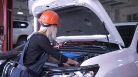 Loja de reparação de automóveis, mecânico da mulher no capacete e macacões que reparam carro quebrado com a capa aberta na estaçã video estoque