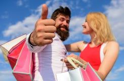 Loja do conselho agora Os pares com sacos de compras afagam o fundo do céu azul O homem com barba mostra o polegar acima do gesto fotografia de stock
