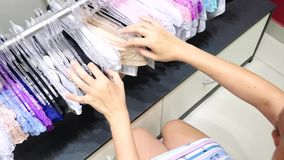 Loja do roupa interior do ` s das mulheres Cuecas do ` s das mulheres nos ganchos em uma loja do sexo, 4k, movimento lento vídeos de arquivo