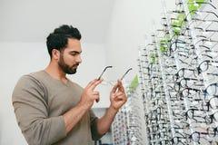 Loja dos vidros Homem que tenta em monóculos na loja do sistema ótico imagens de stock