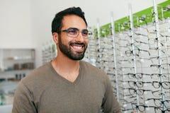 Loja dos vidros Homem que tenta em monóculos na loja do sistema ótico fotos de stock royalty free