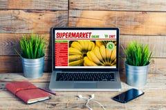 Loja em linha do mantimento do supermercado em uma tela do portátil no escritório fotografia de stock