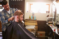 Loja masculina de Barber Giving Client Haircut In imagem de stock