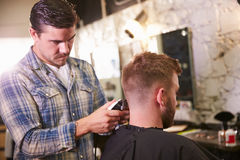 Loja masculina de Barber Giving Client Haircut In fotografia de stock