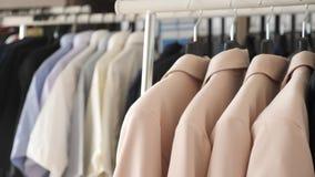 Loja moderna com os ganchos completos da roupa diferente video estoque