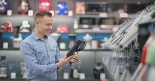 A loja moderna da eletrônica, homem considerável escolhe um misturador para sua esposa filme