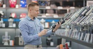 A loja moderna da eletrônica, um homem considerável escolhe um misturador para cozinhar o alimento saudável na cozinha video estoque