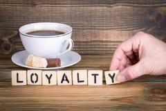 lojalitet Träbokstäver på den informativ och kommunikationsbakgrunden för kontorsskrivbord, royaltyfri fotografi