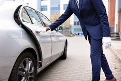 Lokaj r?ka Otwiera Samochodowego drzwi fotografia royalty free
