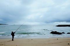 lokal fiskaresportfiskare som gjuter hans drag på en sandig kuststrand på Atlanticet Ocean royaltyfria foton