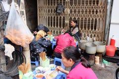 Lokal gatamatförsäljare på ett hörn i Hanoi gamla fjärdedel Fotografering för Bildbyråer