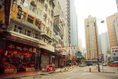 Lokal kines shoppar och folk som går på gator med högväxta konkreta byggnader i asiatisk stad Arkivfoton