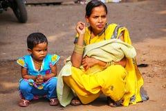 Lokal kvinna med ett flickasammanträde på gatamarknaden i Fatehpur Royaltyfri Fotografi