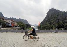 Lokal kvinnlig vietnames med den traditionella hatten som rider en cykel på den Hoa Lu tempelbron, sjö som omges av kalkstenar -  Royaltyfri Foto