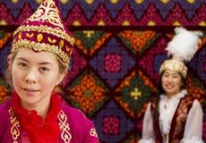 Lokal kvinnor och man i traditionell kläder på nationella folkloric lekar i Almaty, Kasakhstan arkivfoto