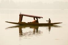 Lokal man i det lilla fartyget för trans. i sjön av Srinagar, Jammu and Kashmir stat, Indien Arkivbild