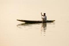 Lokal man i det lilla fartyget för trans. i sjön av Srinagar, Jammu and Kashmir stat, Indien Arkivfoton