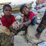 Lokala barn gräver i sanden på bankerna av helgedomen Ganges River för att finna mynt som kastas som en gåva till gudarna vallfär Arkivbild