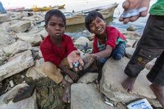 Lokala barn gräver i sanden på bankerna av helgedomen Ganges River för att finna mynt som kastas som en gåva till gudarna vallfär Royaltyfri Fotografi