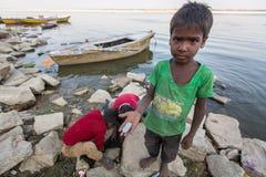 Lokala barn gräver i sanden på bankerna av helgedomen Ganges River för att finna mynt som kastas som en gåva till gudarna vallfär Royaltyfri Foto