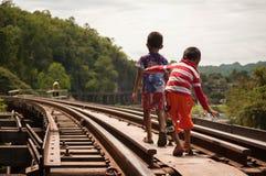 Lokala barn som går på järnvägen i Kanchanaburi Fotografering för Bildbyråer
