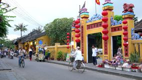 Lokala folk, turister, sparkcyklar och cyklar på gatorna av Hoi An Old Town, Vietnam arkivfilmer