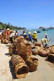 Lokala kvinnor gör ren deras korgar som användes för transportering av fiskar från fartyget till lastbilen Arkivfoto