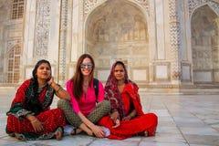 Lokala kvinnor och ett utländskt flickasammanträde utanför Taj Mahal i Agra Fotografering för Bildbyråer