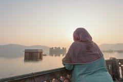 Lokala kvinnor som besöker Jal Mahal, bevattnar slotten under soluppgång på Ja Arkivbilder