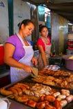 Lokala kvinnor som lagar mat kött för asado på Mercado 4 i Asuncion, medeltal Royaltyfri Fotografi