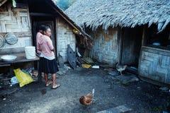 lokale Dorfmädchen, die nahe bei ihrem traditionellen gesponnenen Palme-Hüttenbambushaus mit Huhn warten lizenzfreies stockfoto