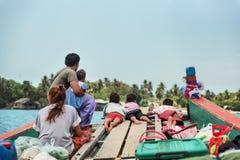 Lokale dorpsbewoners die op een houten vlot zwemmen Royalty-vrije Stock Fotografie