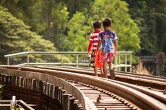 Lokale Kinder, die auf die Eisenbahn in Kanchanaburi gehen Lizenzfreie Stockfotografie